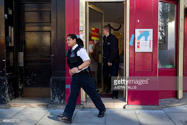 Police officers leave the constituency office of British Labour Party member of parliament Neil Coyle in London on December 4 after the politician...