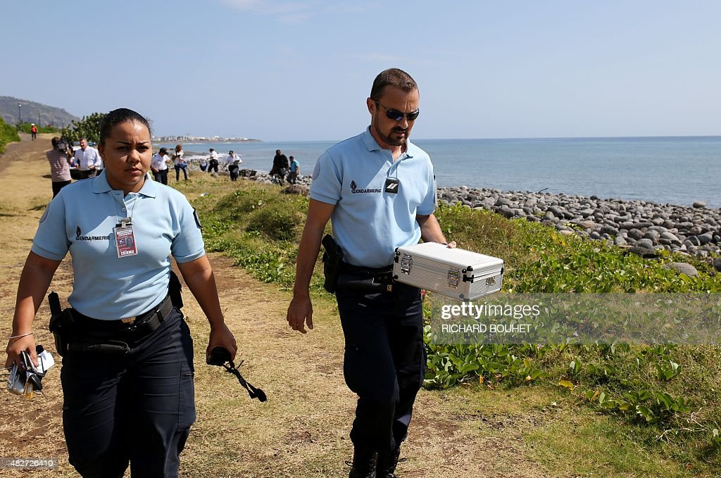 Police officers leave the scene with container holding metallic debris found on a beach in SaintDenis on the French Reunion Island in the Indian...