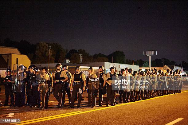 Police officers line up strategically during a civil disobedience action on West Florissant Avenue in Ferguson Missouri on August 10 2015 US police...