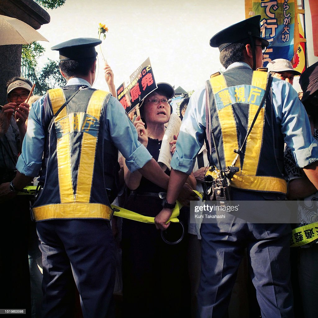 Police officers line up to control anti-nuclear protesters during a mass demonstration on July 29, 2012 in Tokyo, Japan. Police have imposed tight controls on the weekly protest against restarting nuclear power plants. All 54 of Japan's nuclear plants had been offline for months, in the wake of the disaster at the Fukushima Daiichi nuclear plant. Protesters wanted the government to reconsider its energy policy but the government decided to restart the Ohi nuclear plant anyway.