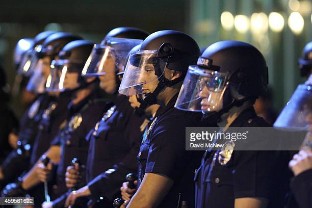 Police officers line up to protect the LAPD Headquarters as they face off with protesters after the grand jury decision not to indict a white police...