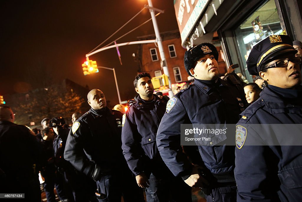 Police officers lineup to pay their respects at a memorial during a vigil for two New York City police officers at the location where they were...