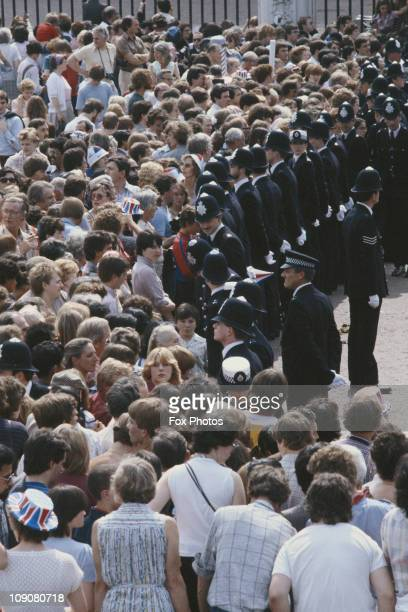 Police officers lining the procession route on the day of Prince Charles' wedding to Lady Diana Spencer London 29th July 1981 Some of the crowd have...