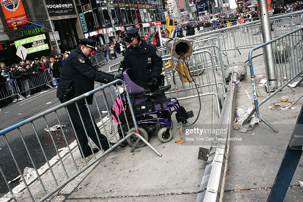 Police officers look at a wheelchair left in Times Square after a woman sitting in it was injured when the cables controlling the MM balloon in the...
