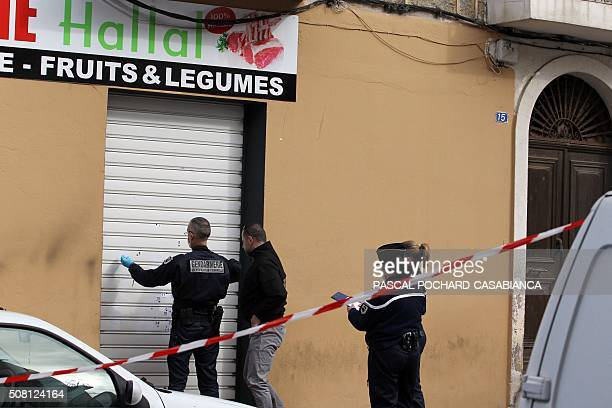 Police officers look for evidence at a Muslim butcher's shop that was sprayed with bullets overnight on February 3 2016 in Propriano on the French...