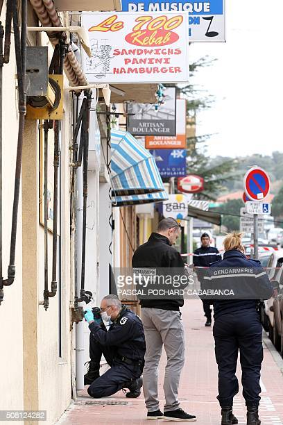 Police officers look for evidence near a Muslim butcher's shop that was sprayed with bullets overnight on February 3 2016 in Propriano on the French...