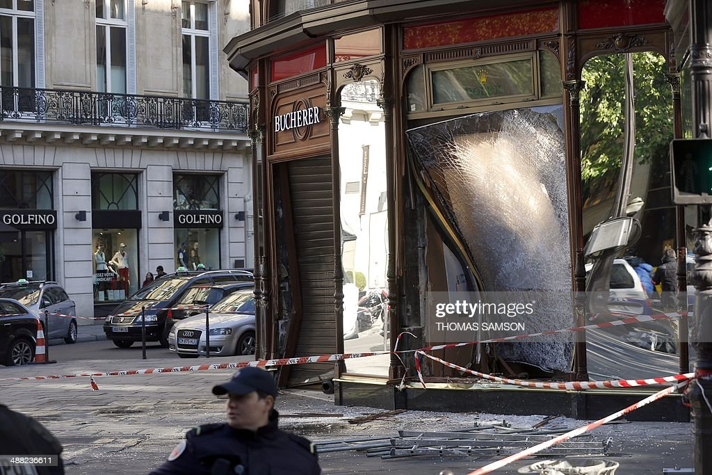Police officers look for evidence outside the jewellery store which was attacked by unidentified men with a motorized battering ram (L) on May 5, 2014 in Paris' Opera district.
