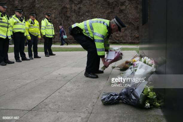 TOPSHOT Police officers look on as a colleague lays a bunch of flowers with other tributes at the National Police Memorial beneath the list of the...