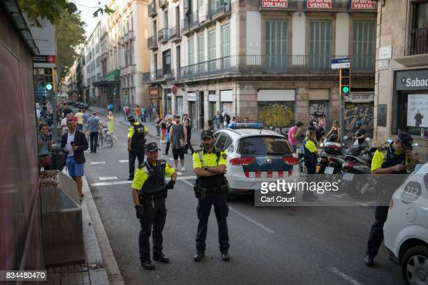 Police officers look on as a group of men have their identity checked on Las Ramblas following yesterday's terrorist attack on August 18 2017 in...