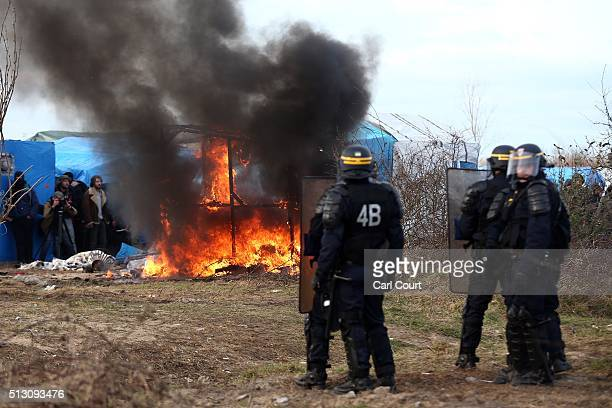 Police officers look on as a hut burns as part of the 'jungle' migrant camp is cleared on February 29 2016 in Calais France The French authorities...