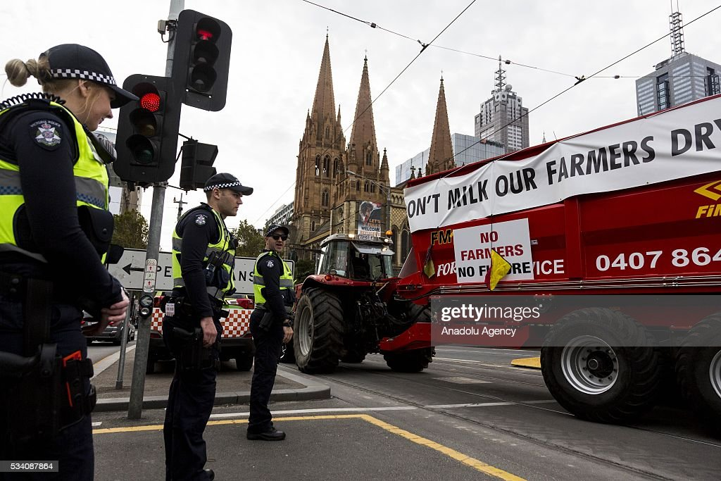 Police officers look on as a large farmers tractor drives through the Melbourne city during a protest demanding Australian government to solve the dairy crisis in Melbourne, Australia on May 25, 2016.