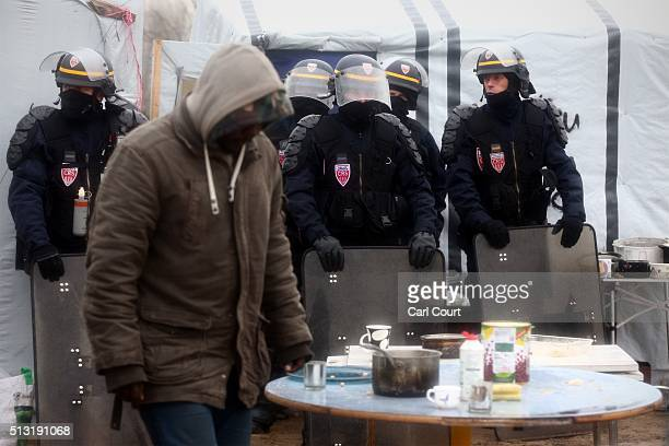 Police officers look on as a migrant carries belongings away from his hut as police and demolition workers clear the 'jungle' migrant camp on March...