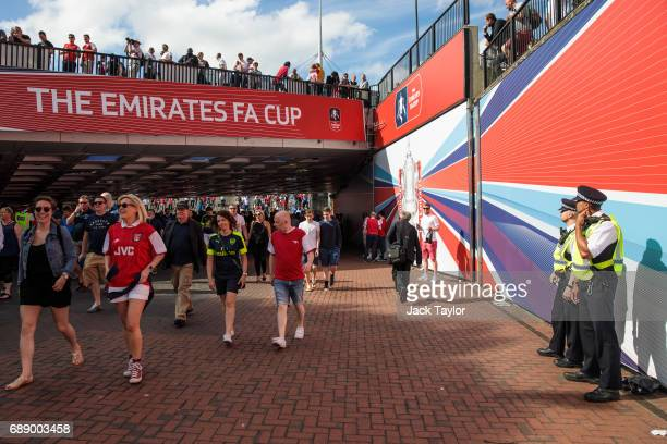 Police officers look on as football fans make their way to Wembley Stadium ahead of the FA Cup final on May 27 2017 in London England Football fans...
