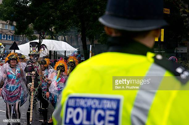 Police officers look on as members of the London School of Samba perform during the parade at Notting Hill Carnival on August 31 2015 in London...