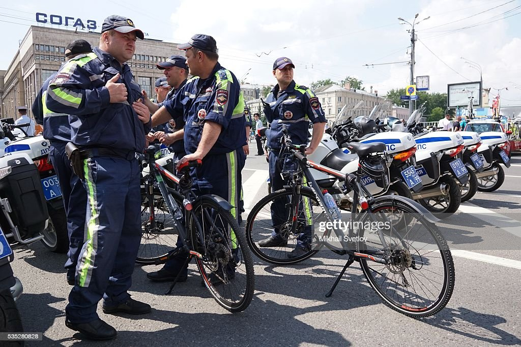 MOSCOW, RUSSIA - MAY, 29 (RUSSIA OUT) Police officers look on as participants of the All-Russian Bicycle Parade 2016 ride at the Garden Ring avenue in Moscow, Russia, May 29, 2016. 30 000 people took part in the parade, cycling 17 km around the central part of Moscow.
