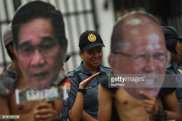 Police officers look on as protesters march towards the Department of National Defense gate in Quezon City north of Manila on 20 July 2017 The...