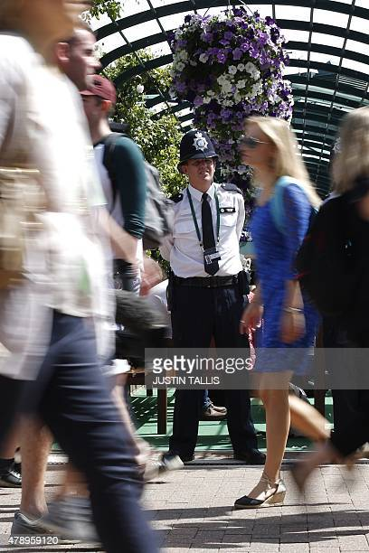 Police officers look on as spectators stream by on day one of the 2015 Wimbledon Championships at The All England Tennis Club in Wimbledon southwest...