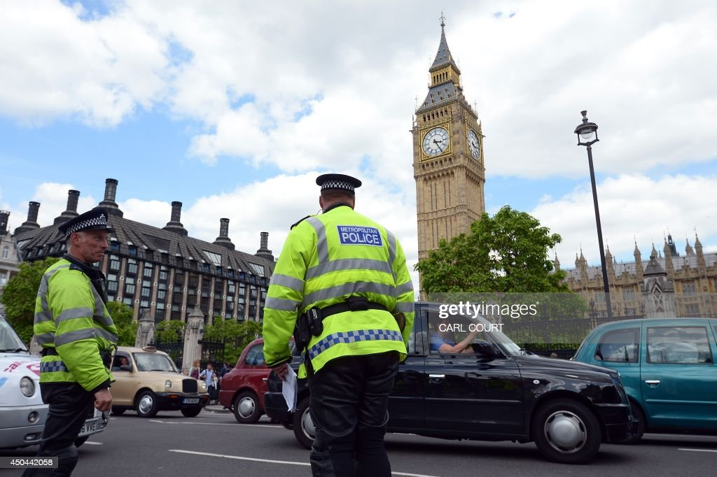 Police officers look on during a protest by London black cab drivers during a protest against a new private taxi service 'Uber', a mobile phone app, in central London on June 11, 2014. Taxi drivers brought parts of London, Paris and other European cities to a standstill on June 11 as they protested against new private cab apps such as Uber which have shaken up the industry. Thousands of London's iconic black cabs, many of them beeping their horns, filled the roads around Buckingham Palace, Trafalgar Square and the Houses of Parliament to the exclusion of any other vehicles.
