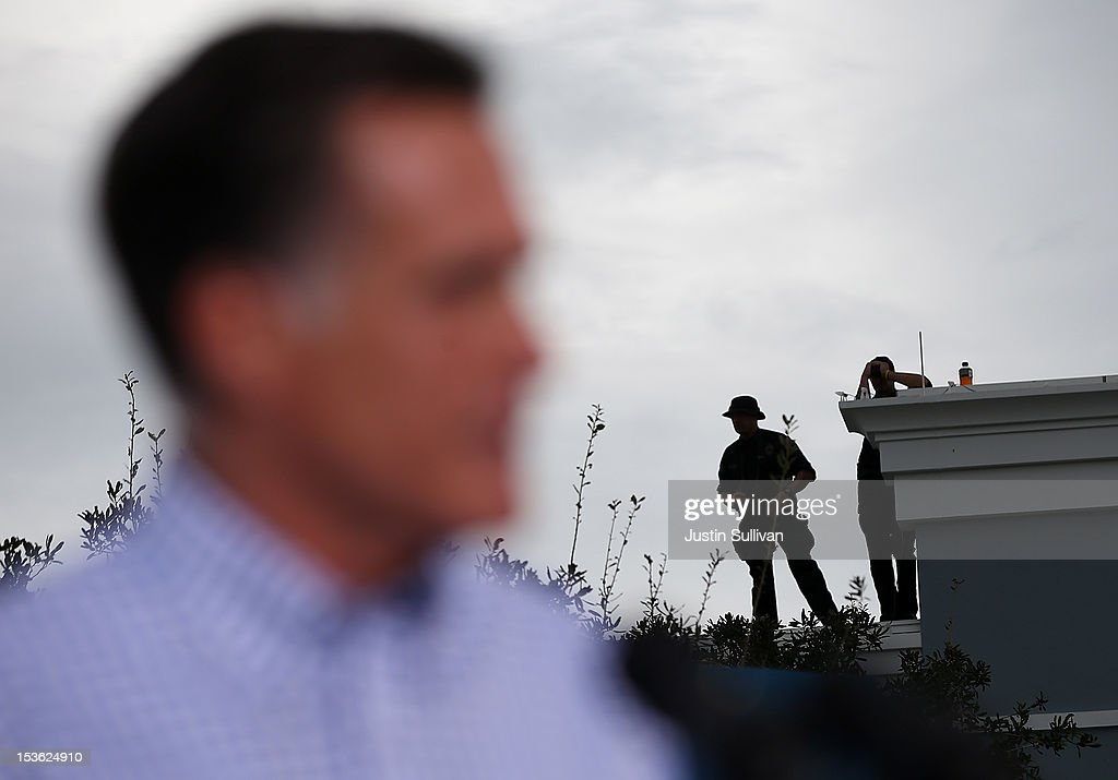 Police officers look on from a rooftop as Republican presidential candidate, former Massachusetts Gov. Mitt Romney speaks during a victory rally at Tradition Town Square on October 7, 2012 in Port St. Lucie, Florida. Mitt Romney is campaigning in Florida before traveling to Virginia where he is scheduled to give a foreign policy speech at the Virginia Military Institute.