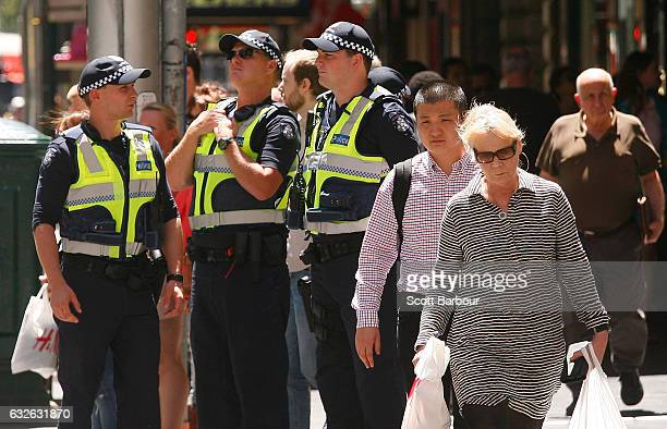 Police officers look on near the floral tributes at Bourke St Mall for victims of the Bourke Street Mall Attack on January 25 2017 in Melbourne...