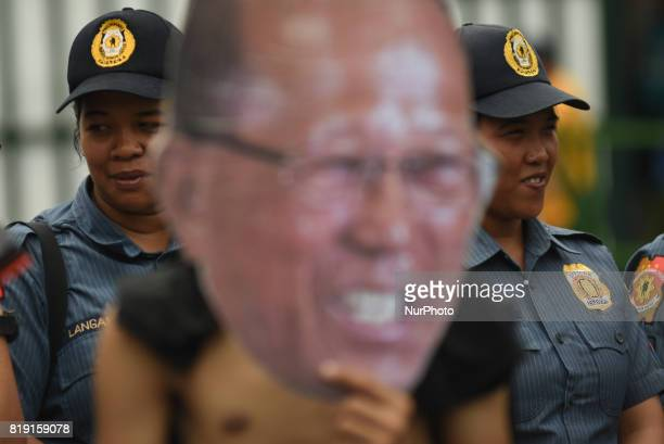 Police officers look on while a man flashes a print out face of Secretary of Defense Delfin Lorenzana as protesters march towards the Department of...