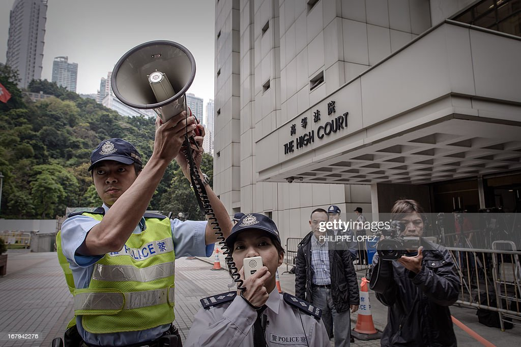 Police officers maintain order as dockers on strike protest outside the High Court in Hong Kong on May 3, 2013. About 450 dock workers are fighting for better pay and working conditions. AFP PHOTO / Philippe Lopez