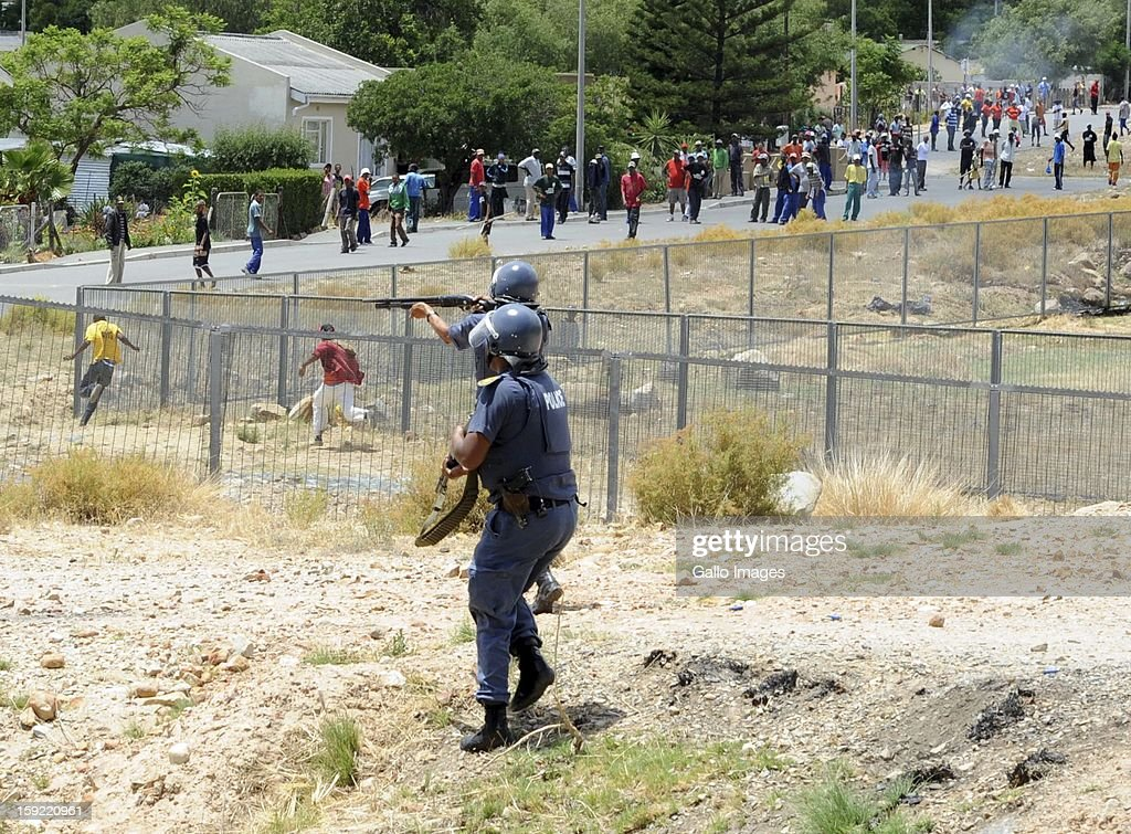 Police officers manage the protestors at the N1 De Doorns highway on January 9, 2013, in Cape Town, South Africa. The farm workers shut down the N1 by lighting tires on fire and placing large rocks on the road.