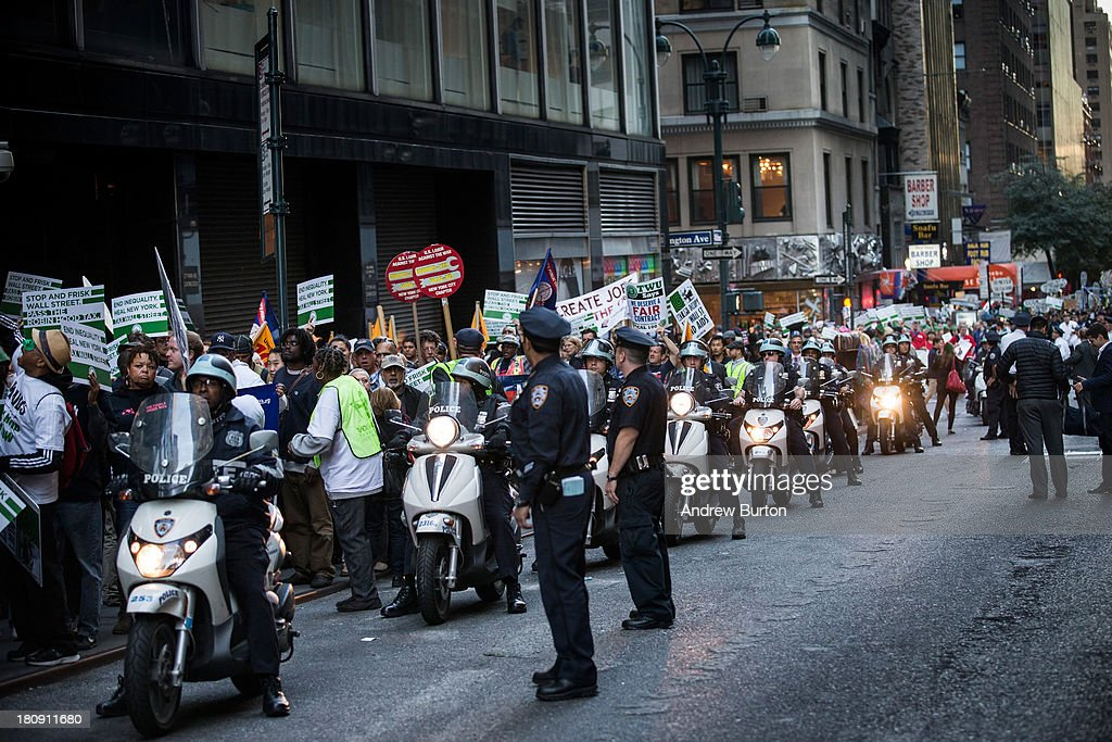 Police officers monitor Occupy Wall Street protesters as they march from the United Nations building to Bryant Park on September 17, 2013 in New York City. The march centered around the idea of a so-called Robin Hood Tax, a 0.5 percent levy to be applied to financial service companies, with proceeds to be used for social services. Today marks the two year anniversary since the protestors set up camp in New York's financial district, calling for drastic social and finanical reform.