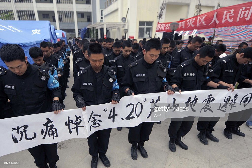 Police officers mourn earthquake victims in Lingguan township of Baoxing county in Yaan, southwest China's Sichuan province on April 27, 2013. China's southwestern Sichuan province stopped on April 27 to mourn the victims of a deadly earthquake that struck exactly a week ago, state media reported. CHINA OUT AFP PHOTO