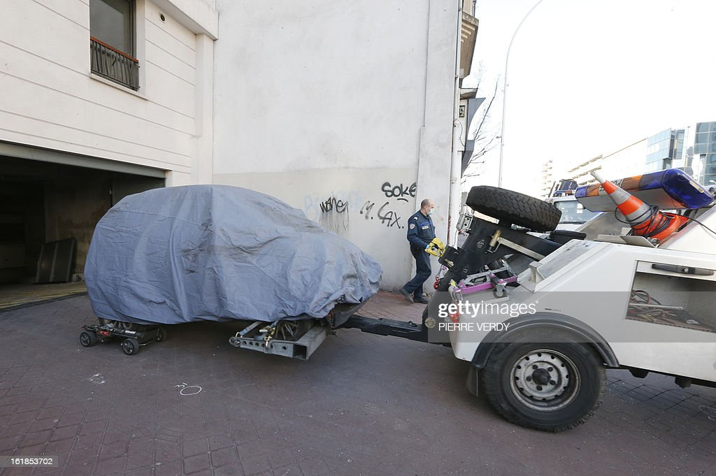 Police officers move a car after searching for evidence on February 17, 2013 in Montrouge, a southern Paris suburb, after a 20-year old woman was seriously wounded in her vehicle by gun shots.