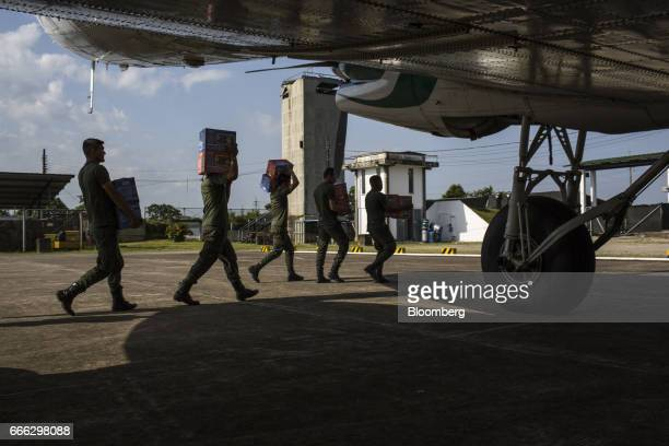Police officers move disaster relief supplies off of a cargo plane at the Villagarzon Airport in Villagarzon Putumayo Colombia on Monday April 3 2017...