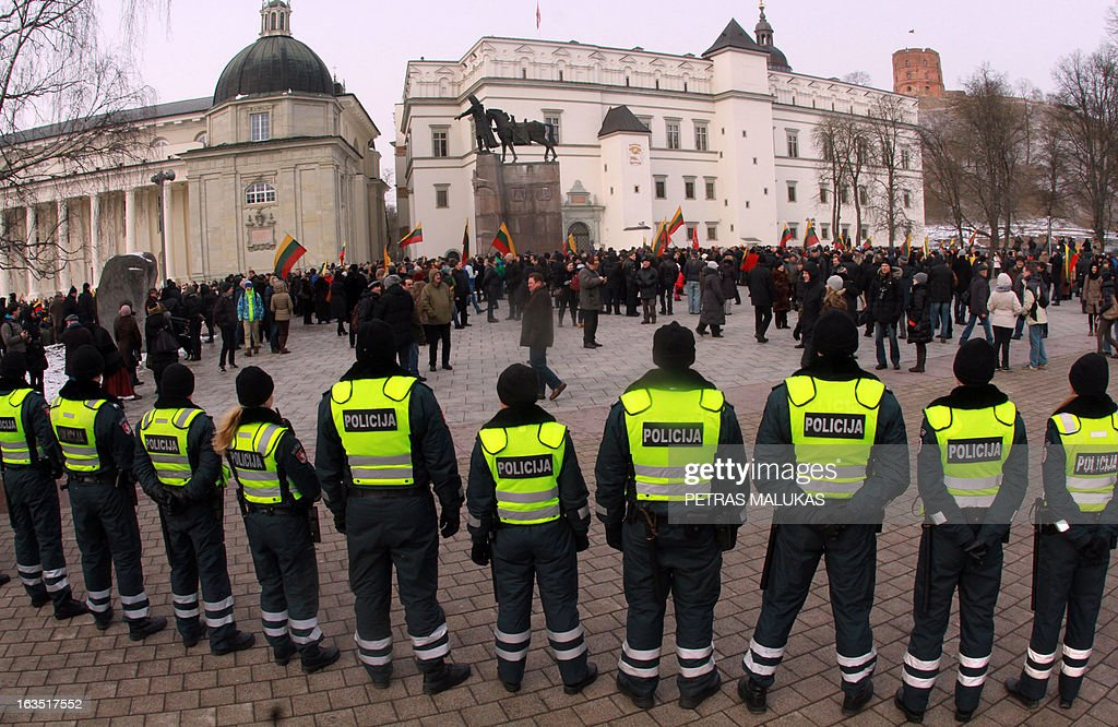 Police officers observe people as they take part in an unauthorized march to commemorate Lithuania's Independence Day in Vilnius on March 11, 2013. Each year on March 11th people commemorate Lithuania's Independence Day.