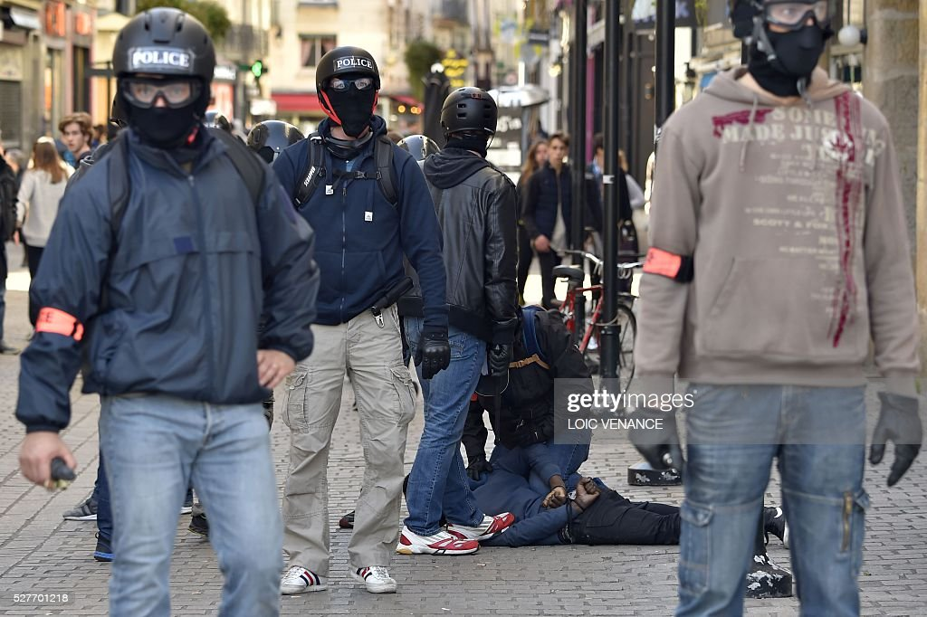 Police officers of France's anti-criminality brigade (BAC) arrest a man during a protest against the government's planned labour law reforms in Nantes, western France, on May 3, 2016. High school pupils and workers protested against deeply unpopular labour reforms that have divided the Socialist government and raised hackles in a country accustomed to iron-clad job security. / AFP / LOIC