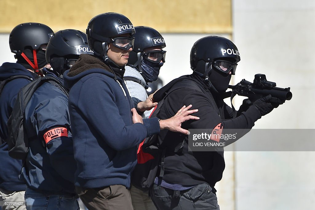 Police officers of France's anti-criminality brigade (BAC) rush to take position during a protest against the government's planned labour law reforms in Nantes, western France, on May 3, 2016. High school pupils and workers protested against deeply unpopular labour reforms that have divided the Socialist government and raised hackles in a country accustomed to iron-clad job security. / AFP / LOIC