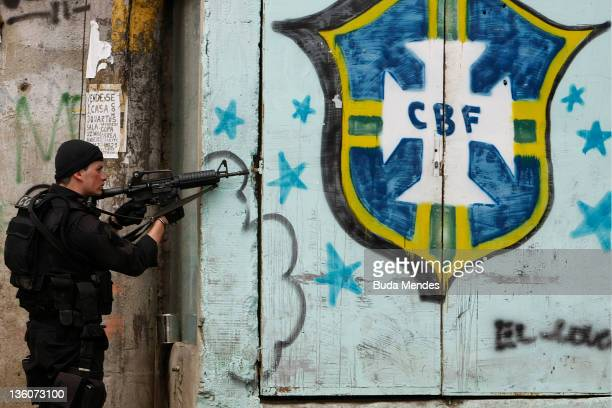 Police officers of the Special Operations Battalion are seen patroling next to a CBF logo at Vila Cruzeiro during the fifth day of a wave of violence...
