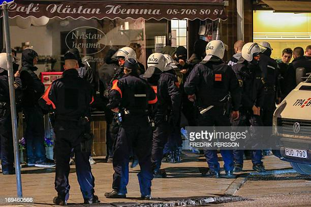 Police officers of the Swedish riot police search young men in the Malarhojden suburb of Stockholm Sweden on early Saturday morning of May 25 the...
