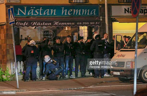 Police officers of the Swedish riot police search young men lined up against a wall in the Malarhojden suburb of Stockholm Sweden on early Saturday...