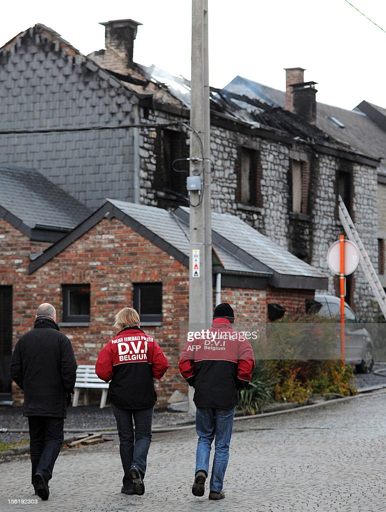 Police officers of the victim identification cell (DVI) walks on the site of a fire that killed four people in a house in the rue des Grottes street in Han-sur-Lesse on November 12, 2012. Belgium Out