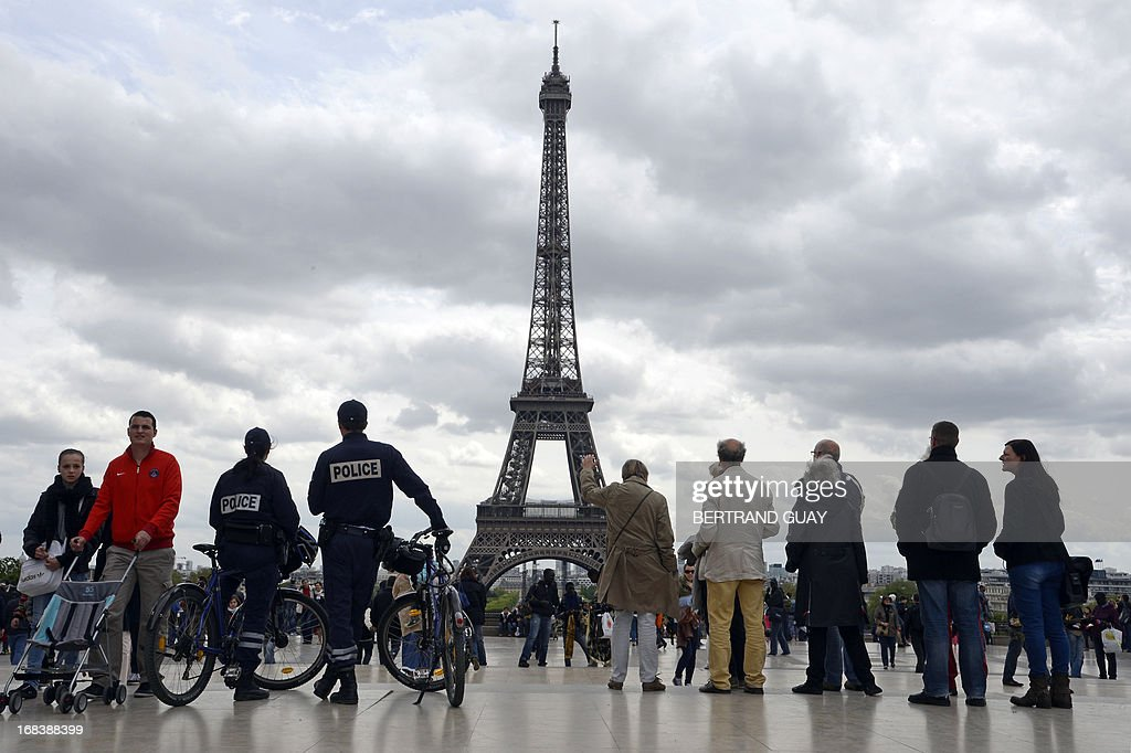 Police officers on bicycles look at people next to the Eiffel Tower, on May 9, 2013 in Paris. AFP PHOTO / BERTRAND GUAY