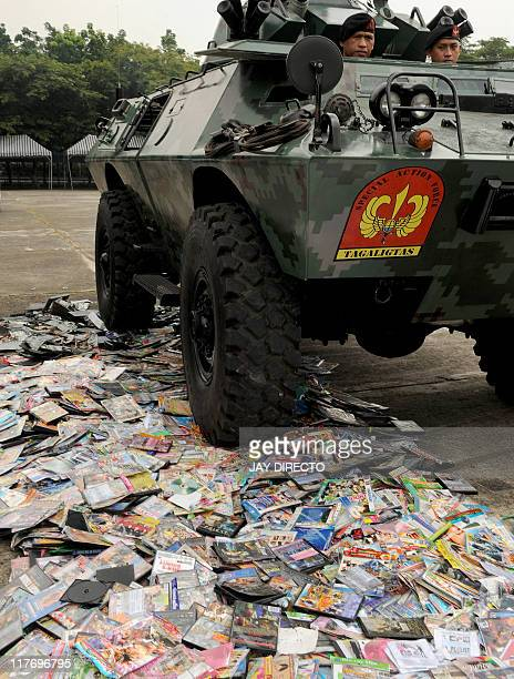 Police officers on board an armored personnel carrier run over counterfeit computer and digital video discs as government officials destroy 8 million...