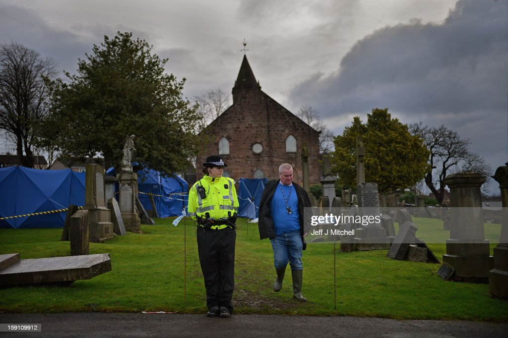 Police officers on duty at Monkland Cemetery as forensic officers start examining a burial plot on January 8, 2013 in Coatbridge, Scotland. Forensic specialist will exhume remains at a grave in North Lanarkshire in search for the body of 11 year old school girl Moria Anderson, who went missing, presumed murdered, in 1957.