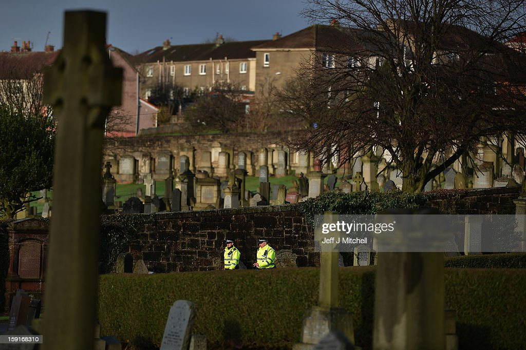 Police officers on duty at Monkland Cemetery as forensic officers continue to exame a burial plot on January 9, 2013 in Coatbridge, Scotland. Forensic specialists are exhuming remains at a grave, in search of 11 year old school girl Moria Anderson who went missing, presumed murdered in 1957.