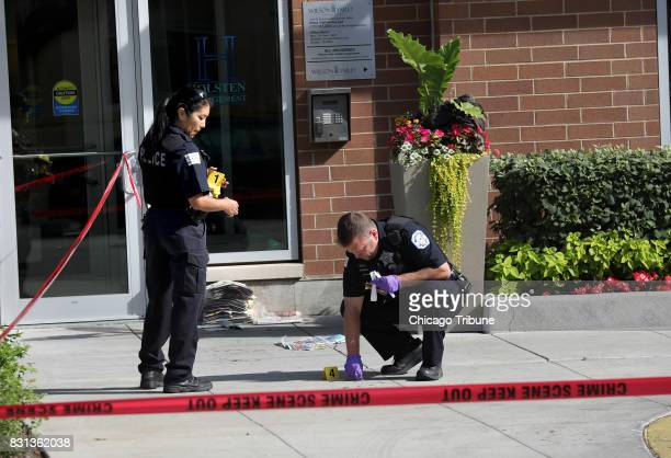 Police officers on the scene take a swab of blood from in front of the door to Wilson Yard A fatal shooting occurred in front of the Wilson Yard...