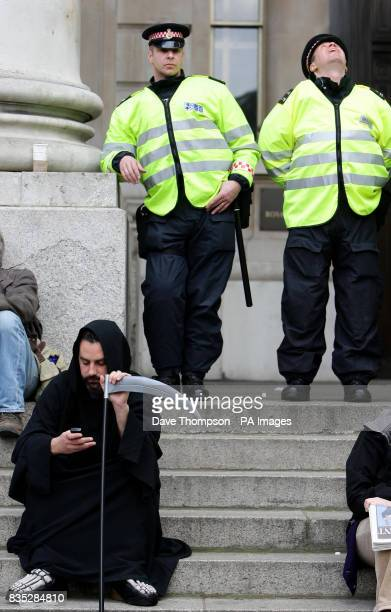 Police officers on the steps outside the Bank Of England with a protester dressed as the Grim Reaper during G20 demonstrations in central London