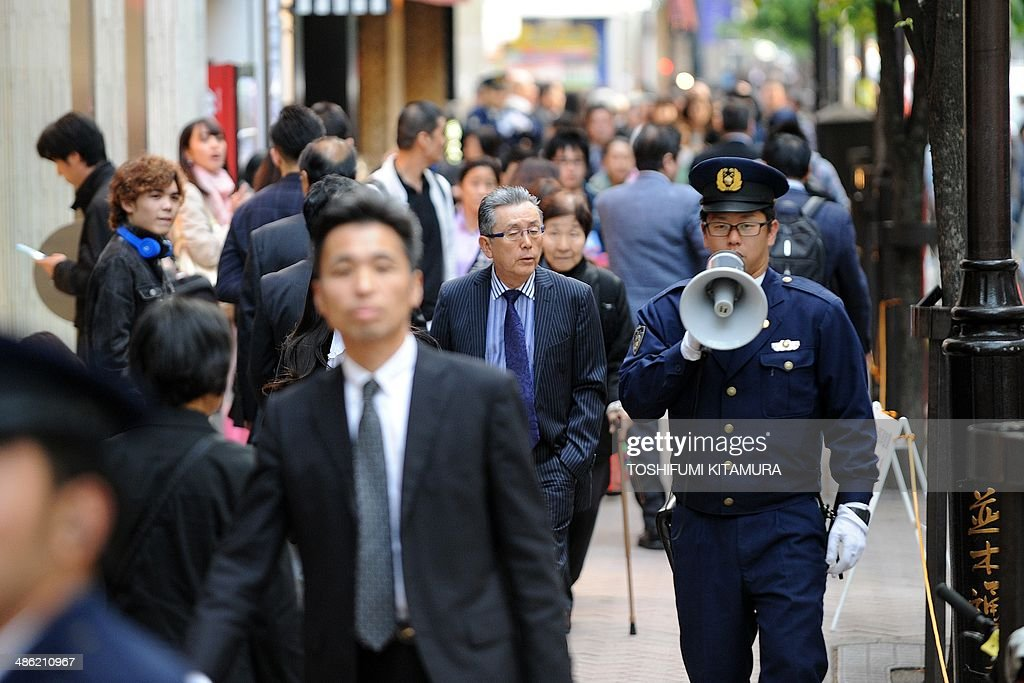 Police officers organizes traffic near the 'Sukiyabashi Jiro' sushi restaurant at Ginza shopping district in Tokyo on April 23, 2014, hours before US President Barack Obama's visit. Obama will reportedly dine at a tiny Tokyo sushi restaurant, a place with three coveted Michelin stars but only a handful of seats, ruled with an iron rod by its redoubtable 88-year-old owner, Jiro. Obama will come to Tokyo for a three-day visit from April 23 for and will have dinner with Japanese Prime Minister Shinzo Abe.