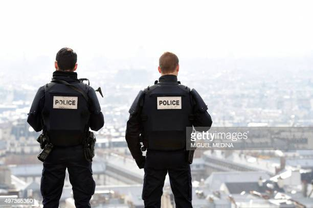 Police officers overlook Paris as they patrol in front of the Sacre Coeur Basilica on November 16 three days after a series of deadly oordinated...