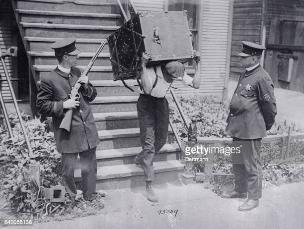 Police officers oversee a Black resident of the South Side of Chicago moving shortly after the riots of 1919