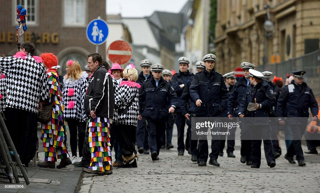 Police officers pass a group of revellers during a carnival parade called 'Schull- un Veedelszoech' as part of the carnival season on February 7, 2016 in Cologne, Germany. Carnival partying and parades, a centuries-old tradition in western and southwestern Germany, traditionally occurs in February and runs until Ash Wednesday, the start of Lent, and culminates in Rose Monday parades and festivities. Police are on added alert this year, particularly in Cologne, due to the New Year`s Eve sex attacks on women that have been attributed to gangs of North African men, predominantly from Algeria and Morocco.
