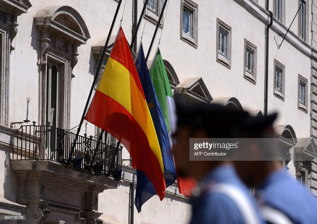 Police officers pass the Spanish, European Union and Italian flags at half mast on the facade of the Italian parliament on August 18, 2017 in Piazza Montecitorio in Rome, one day after a van ploughed into a crowd in Barcelona, killing 13 persons and injuring over 100 on the Rambla boulevard. Drivers have ploughed on August 17 into pedestrians in two quick-succession, separate attacks in Barcelona and another popular Spanish seaside city, leaving 13 people dead and injuring more than 100 others. In the first incident, which was claimed by the Islamic State group, a white van sped into a street packed full of tourists in central Barcelona on the afternoon of August 17, knocking people out of the way and killing 13 in a scene of chaos and horror. Some eight hours later in Cambrils, a city 120 kilometres south of Barcelona, an Audi A3 car rammed into pedestrians, injuring six civilians -- one of them critical -- and a police officer, authorities said. /