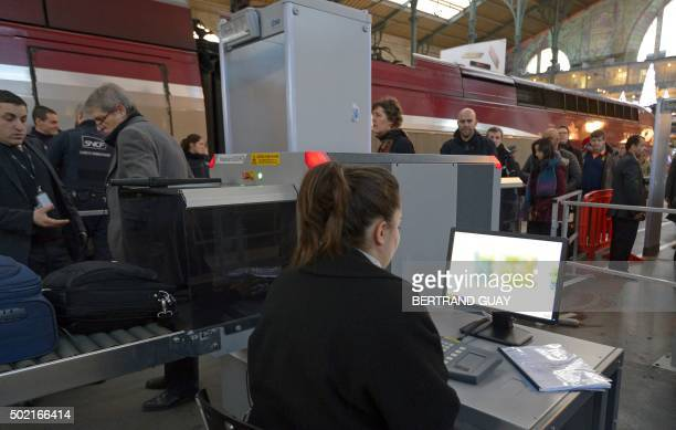 Police officers patrol a checkpoint as passengers walk through a security gate and pass a baggage scanner on December 21 2015 at the Gare Du Nord's...